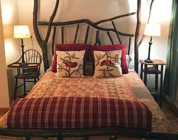Bed with a unique headboard made of tree banches with a table and vintage wooden highchair as nightstands.