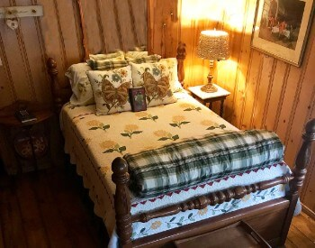 Pretty bed with a flowered quilt and butterfly accent pillows in a wood paneled room.