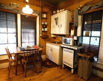Kitchen with wooden floors, white cabinets and a small table with thee chairs.
