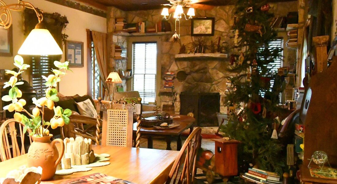Living and dining room area with seating, a decorated pine tree and large rock fireplace.