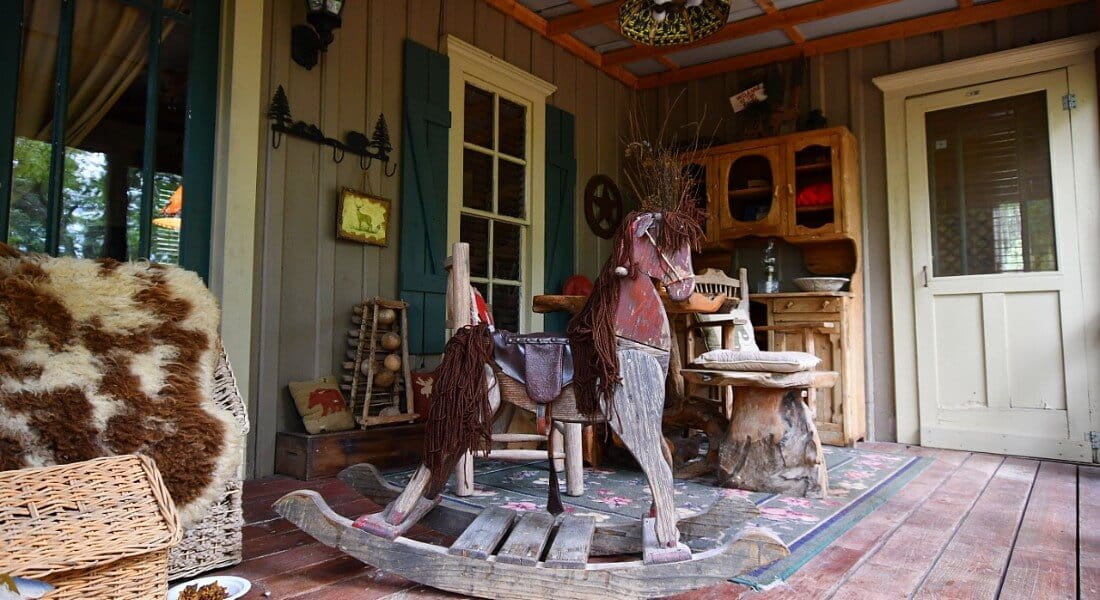 Cabin porch with a rocking horse, hoosier cabinet and wooden seating.