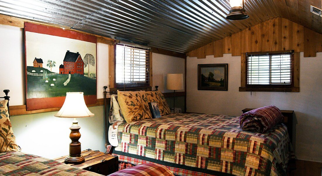 Cozy bedroom in cabin with two beds made up in green, red and white quilts.