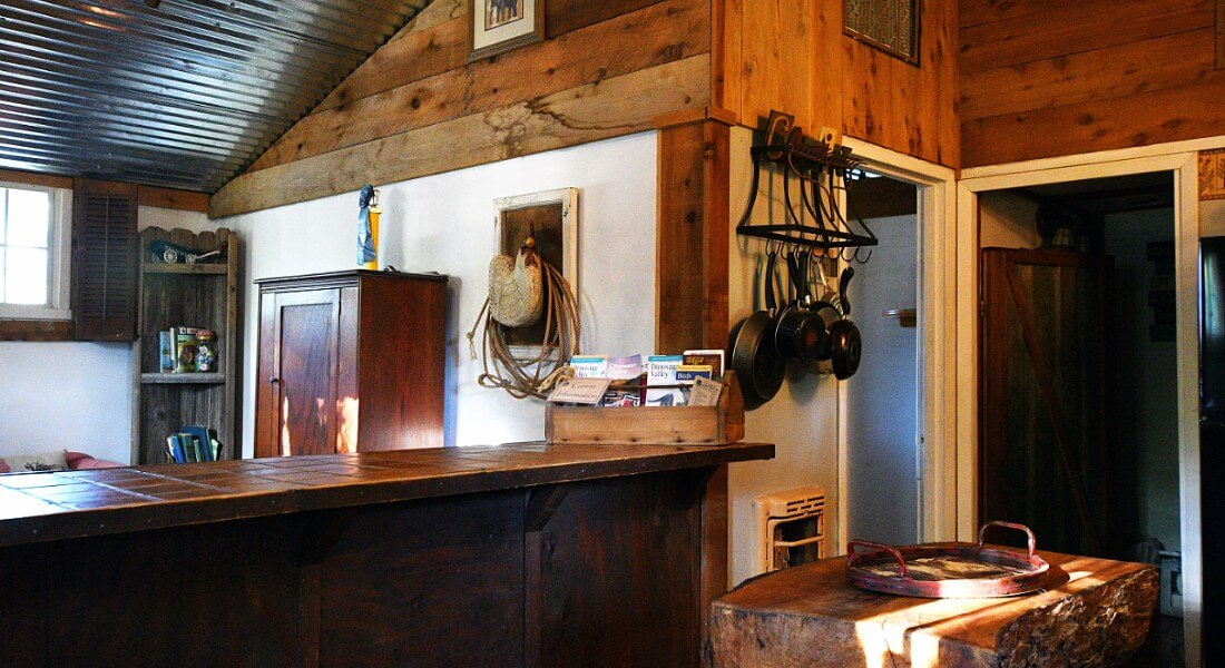 Cabin with a bar, wooden cabinets and pot rack on wall.