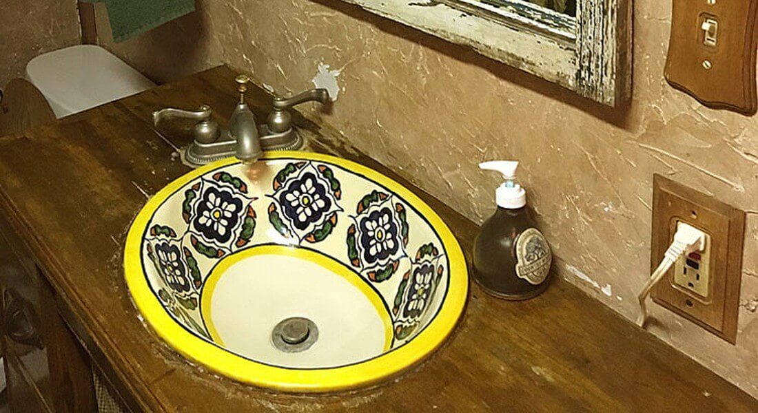 Unique painted mexican vanity sink set into a wooden counter next to a plastered wall.