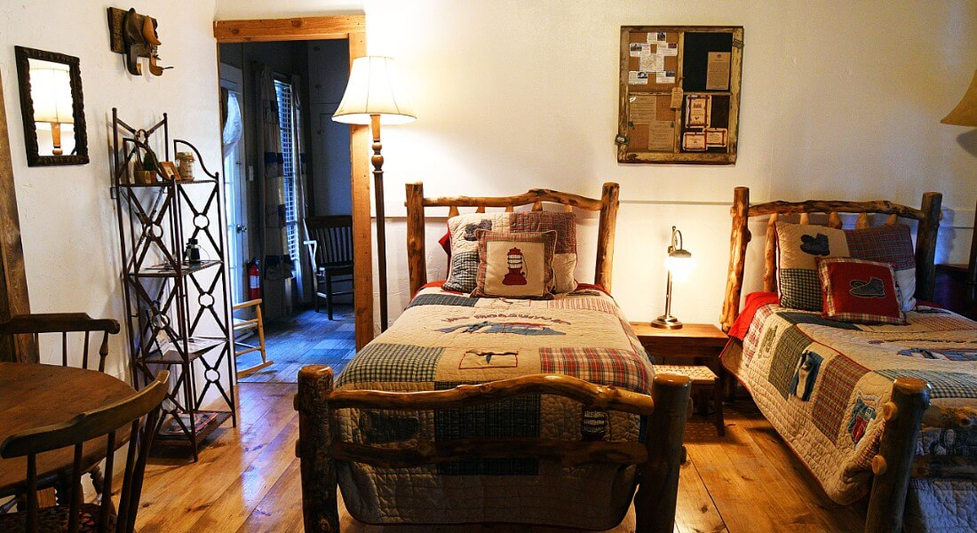 Twin log beds made up with quilts in a bedroom with white walls.