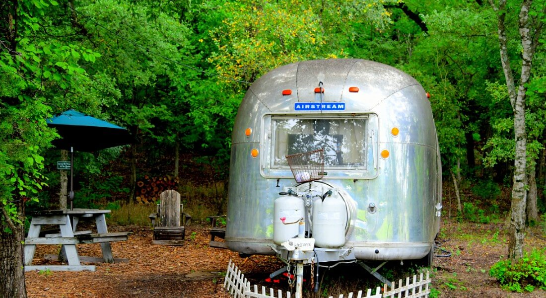 1976 Land Yacht Airstream converted to lodging, set in woods with a picnic table.