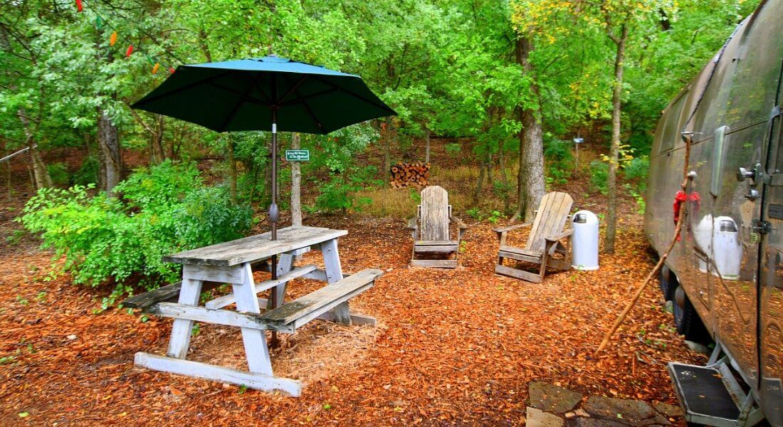 Picnic table with a blue umbrella and two Adirondack chairs in the woods next to a converted trailer.