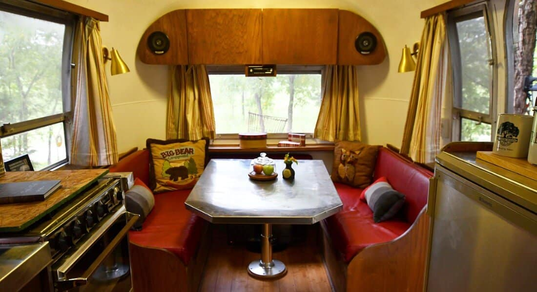 Vintage metal table and wooden benches in a converted Land Yacht Airstream.