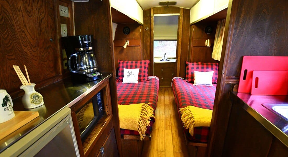 Cozy kitchen with wooden cabinets leads to sleeping area with two beds made up in buffalo check quilts.