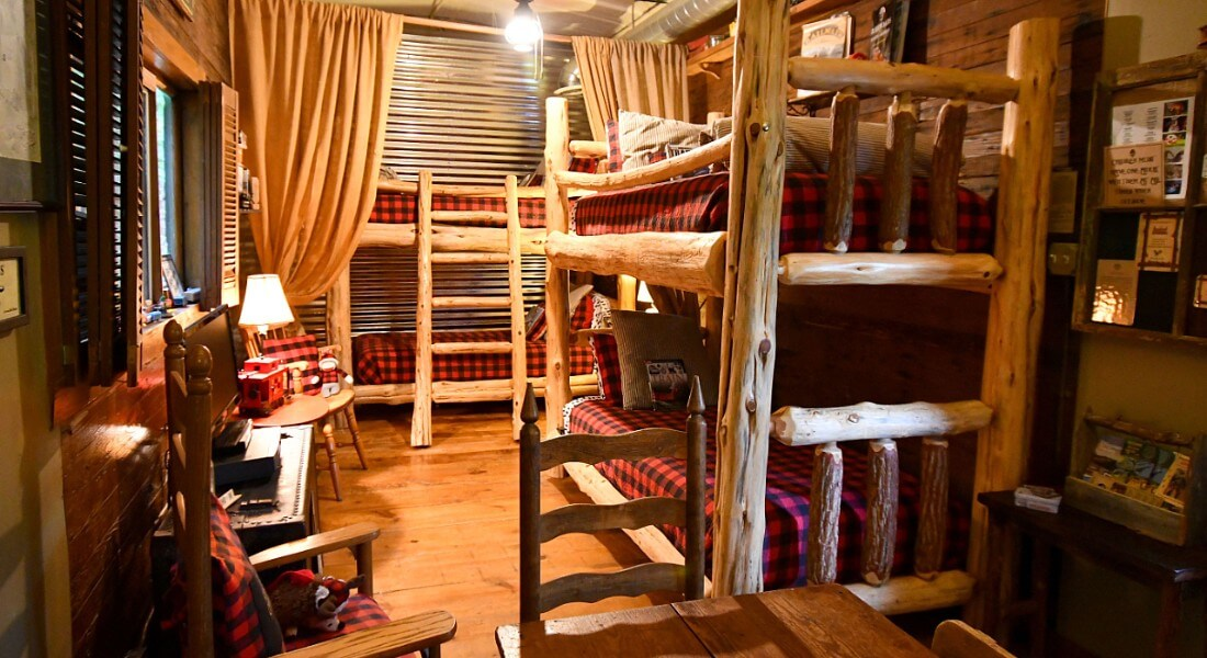 Two rustic pine-log bunk beds made up in red buffalo check quilts in a cozy nook.