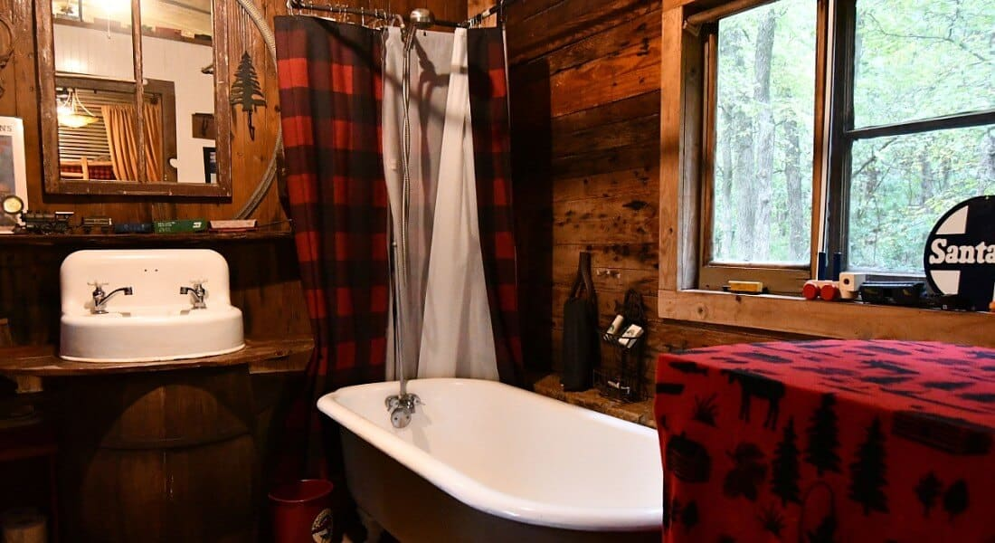 Cozy bathroom contains a clawfoot tun with a shower, a white vanity sink and large window.