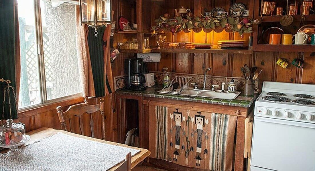 Cabin kitchen with open wood cabinets and a tie counter top next to a white stove.