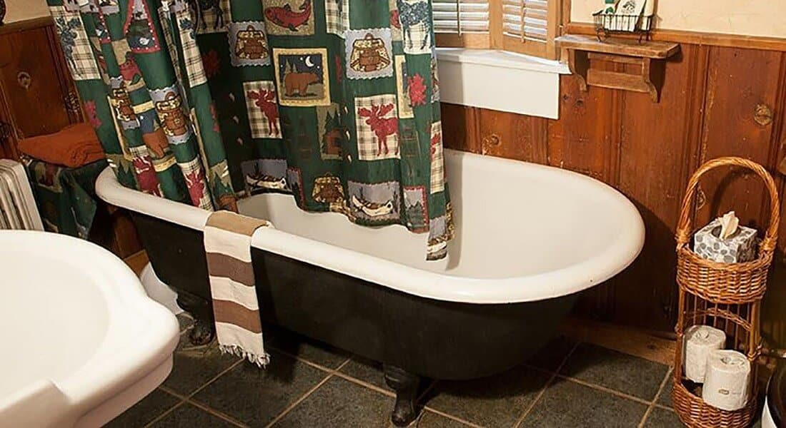 Black clawfoot tub with whimsical forst shower curtain in a bathroom with a white sink and tile floor.
