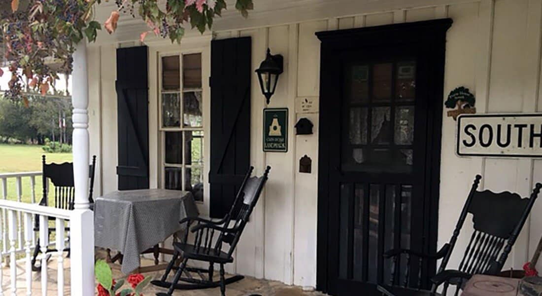 Exterior of cabin with white wooden siding and black door and shutters with rocking chairs on porch.