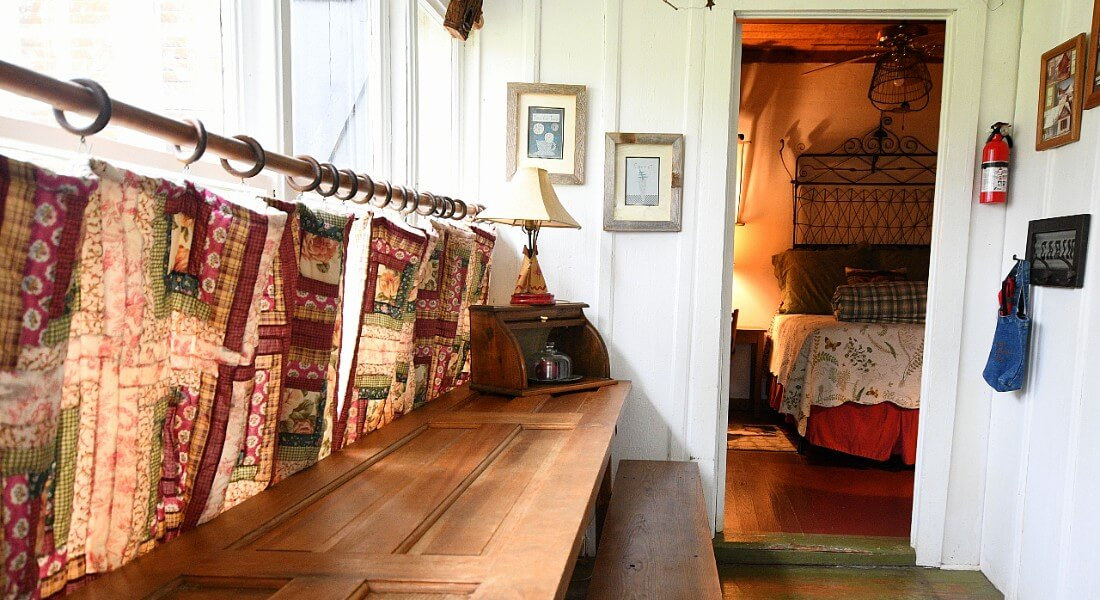 Quilted curtains hang from large light-fille windows over a wooden table and bench.