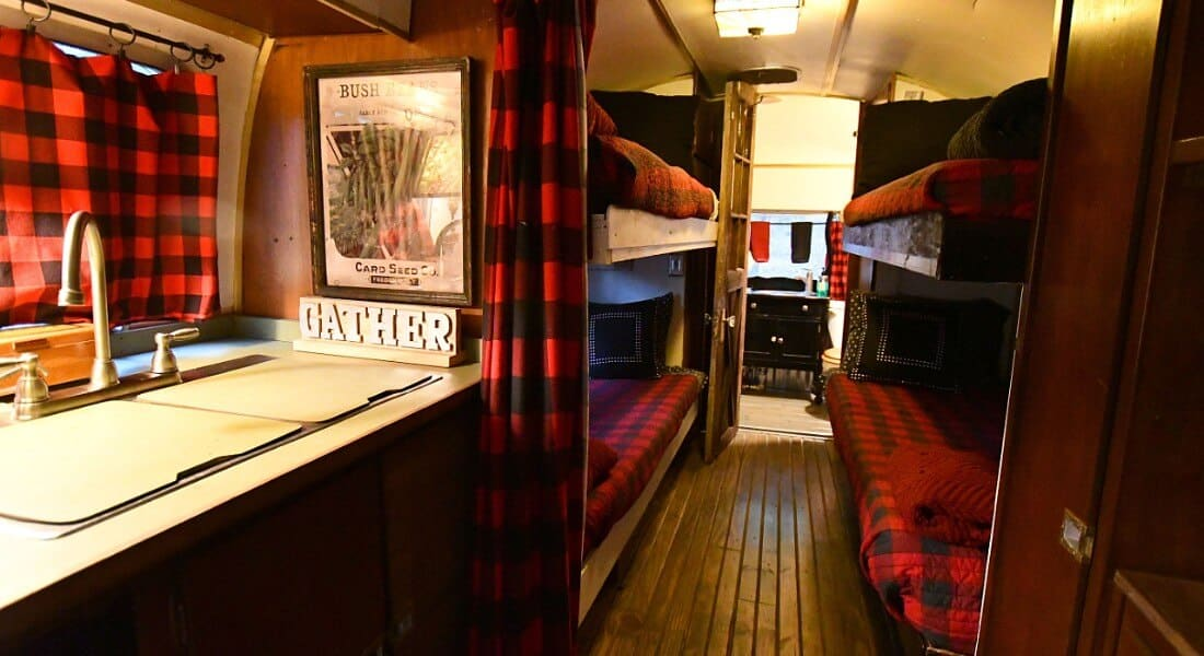 Bunk beds on Sovereign Airstream trailer made up in red buffalo check quilts.
