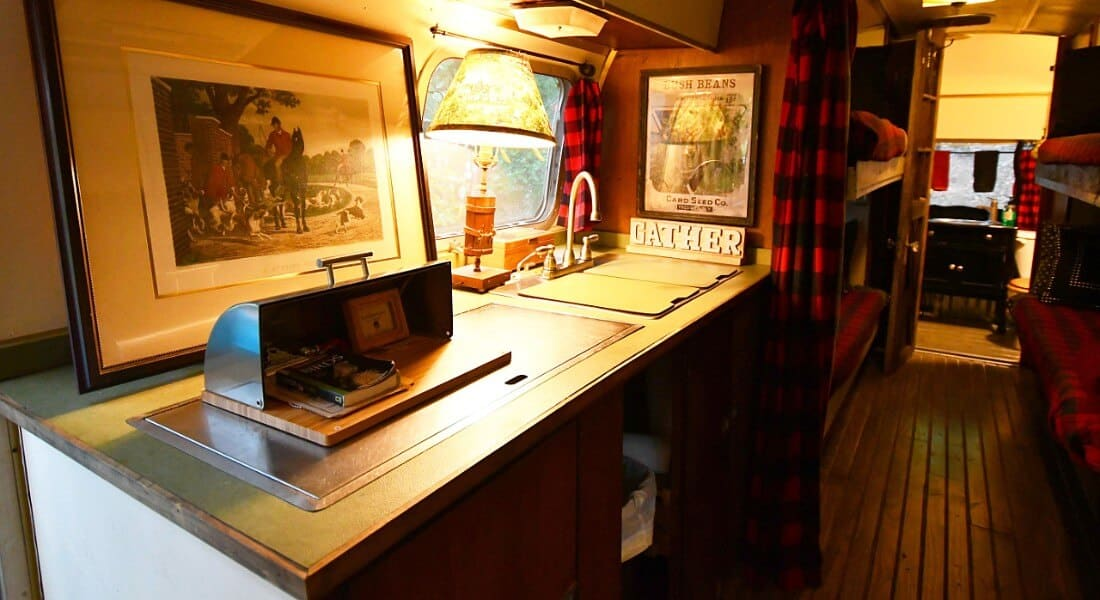 Kitchen area of Sovereign Airstream converted to a lodging, with wooden cabinet and buffalo check accents.
