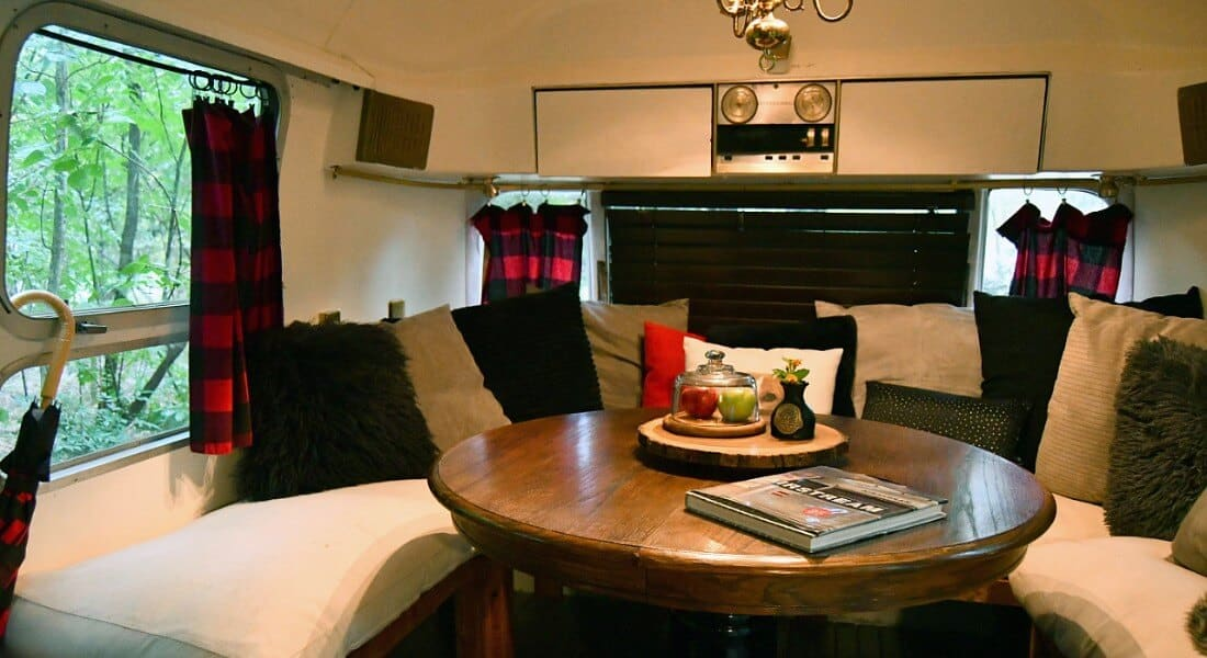 Cozy seating area in Sovereign Airstream trailer with an unhostered bench wrapped around a wooden table.