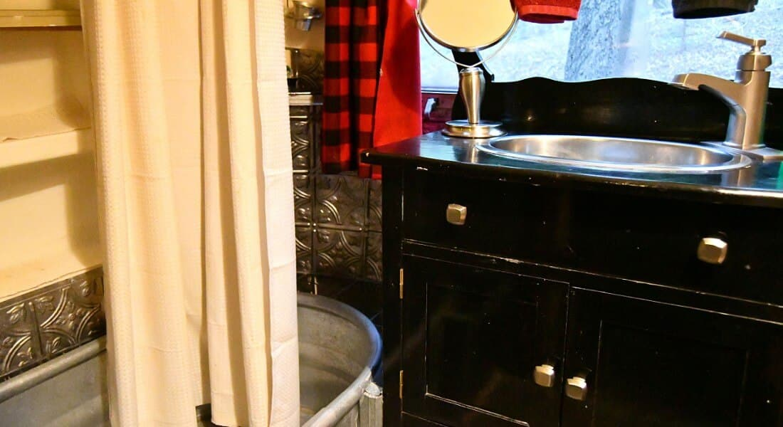 Unique bathroom with stock tank converted to a bathtub and a black vanity cabinet with a metal sink.