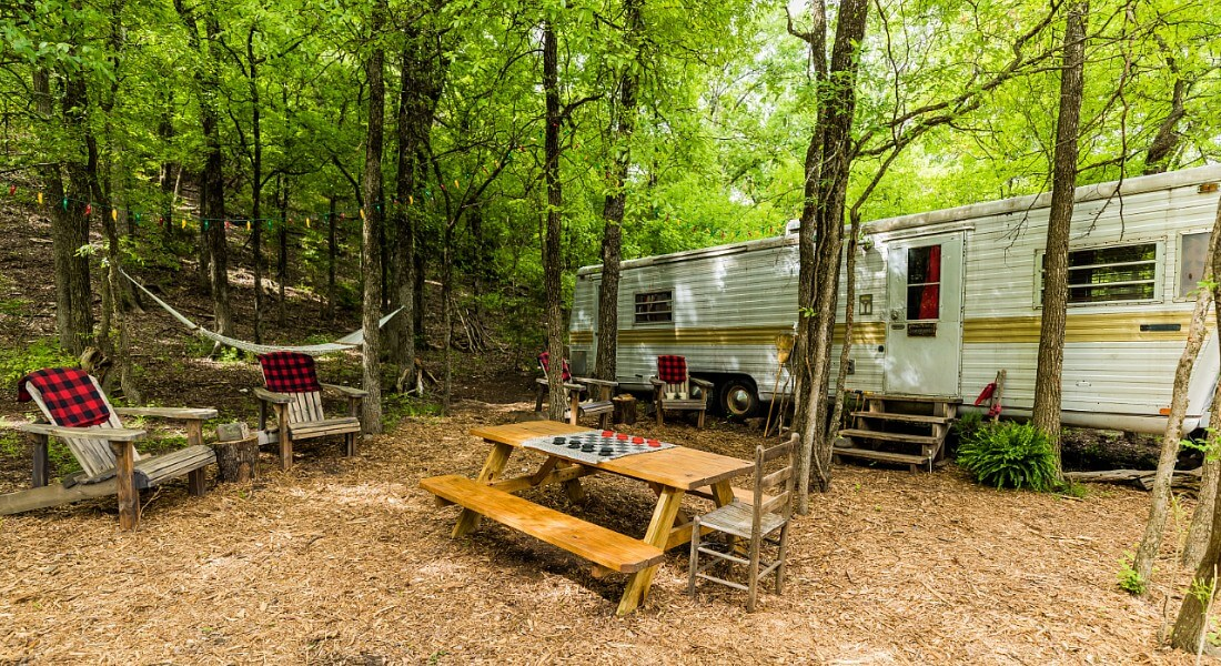 Converted 1975 Spartan Airstream trailer in shaded glen with wooden adirondack chairs and a picnic table.