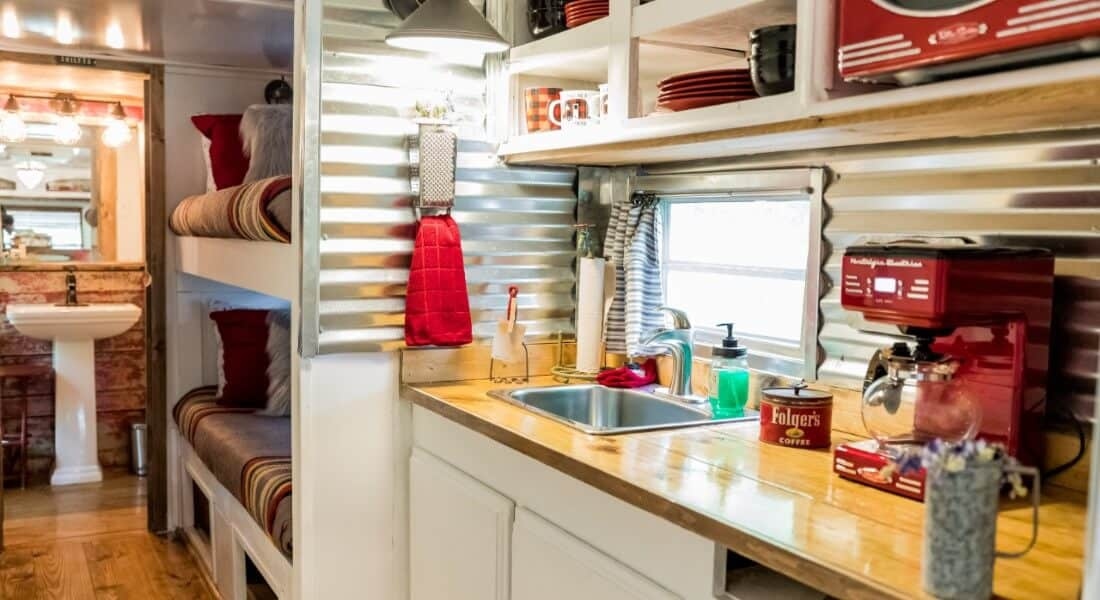 1975 Spartan Airstream kitchen with butcherblock counter, white cabinets and red accents.