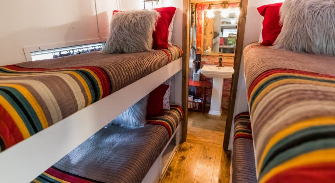 View of bathroom through bunk area in a 1975 Spartan Airstream made into a lodging.