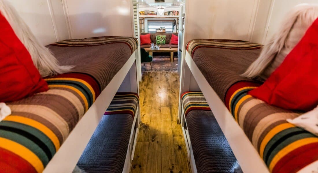 Bunk beds covered with colorful quilts and pillows in a remodeled 1975 Spartan Airstream.