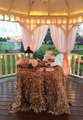 Table decorated for a wedding with a white wedding cake in a gazebo.