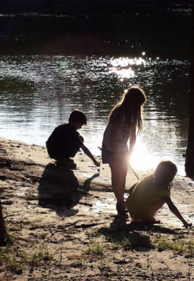 Three children play in the sand on the bank of a river.