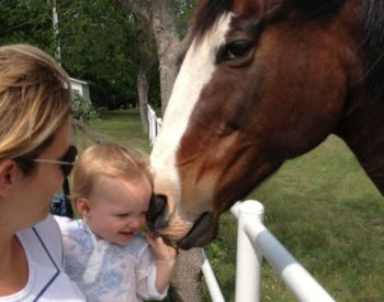 A blonde woman holds a baby close to a chesnut horse with a white blaze.