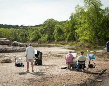 People paint, wade and sit next to a stream surrounded by green trees.