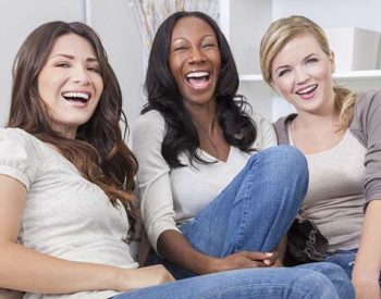 Three young ladies in jeans laugh together on a sofa.