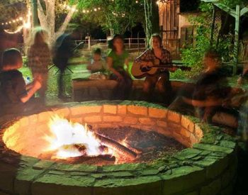 A group of people around a firepit, singing and playing the guitar.