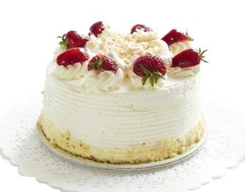 A cake frosted in white with crumb and strawberry decorations.