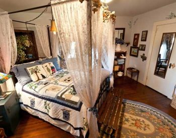 Homey bedroom with a bed canopied in lace covered with a quilt and a painted bedside table.
